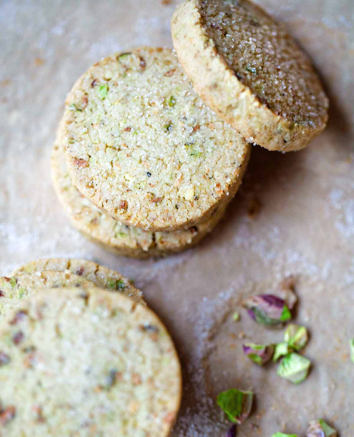Five round pistachio shortbread cookies with a few broken pistachios on the side