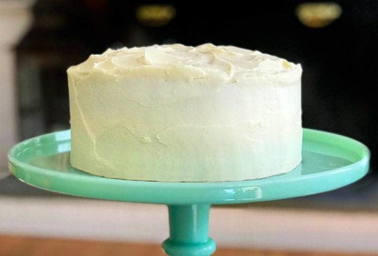 A pumpkin cake with maple-cream cheese frosting on a teal cake stand.