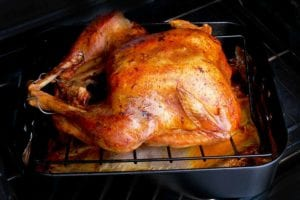 A simple roast turkey on a rack set over a roasting pan in the oven.