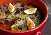 Crockery filled with bacalhau a Gomes de Sa--layers of salt cod, potato, and, onions; on top, sliced olives, quartered boiled eggs, parsley on wood