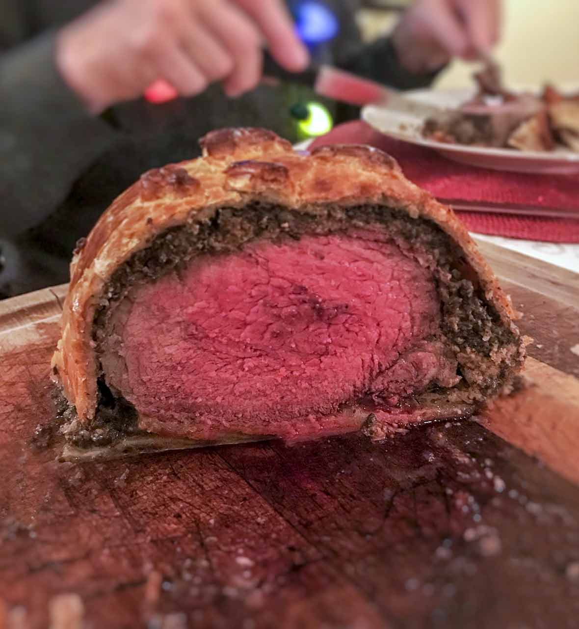 A beef tenderloin covered in pate and chopped mushrooms and wrapped in puff pastry on a cutting board
