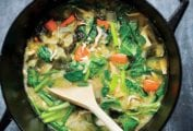 A steel wok filled with mushrooms, greens, broth, and carrots, with a wooden spoon resting inside