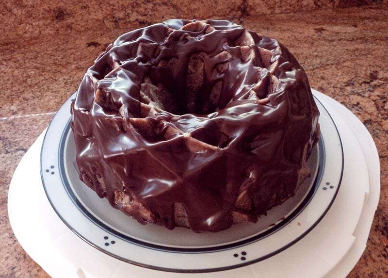 A chocolate jubilee Bundt cake topped with chocolate ganache sitting on a white plate