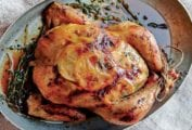 Roast chicken with lemon slices under the skin in a oval metal pan