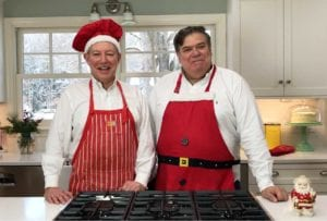 The One in a red apron and red chef's hat and David Leite in a Santa apron in their kitchen
