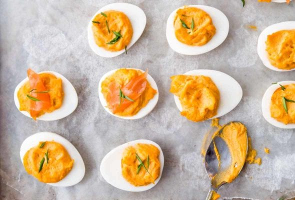 Nine deviled egg halves and a teaspoon on a parchment-lined baking sheet