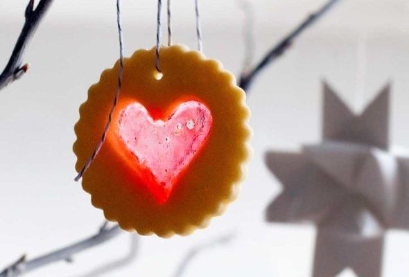 A scalloped round sugar cookie with a heart-shaped windowpane cutout hanging form a tree branch