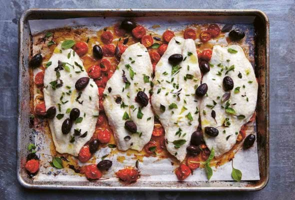 Fish fillets on a sheet pan with roasted tomatoes and black olives