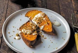 Two halves of a sweet potato drizzled with maple-yogurt sauce and topped with granola on a plate on a wooden table