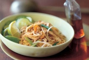 Pad Thai noodles, crunchy noodles. cucumber, bean sprouts, and lime wedges in a bowl, a bottle of chile-vinegar