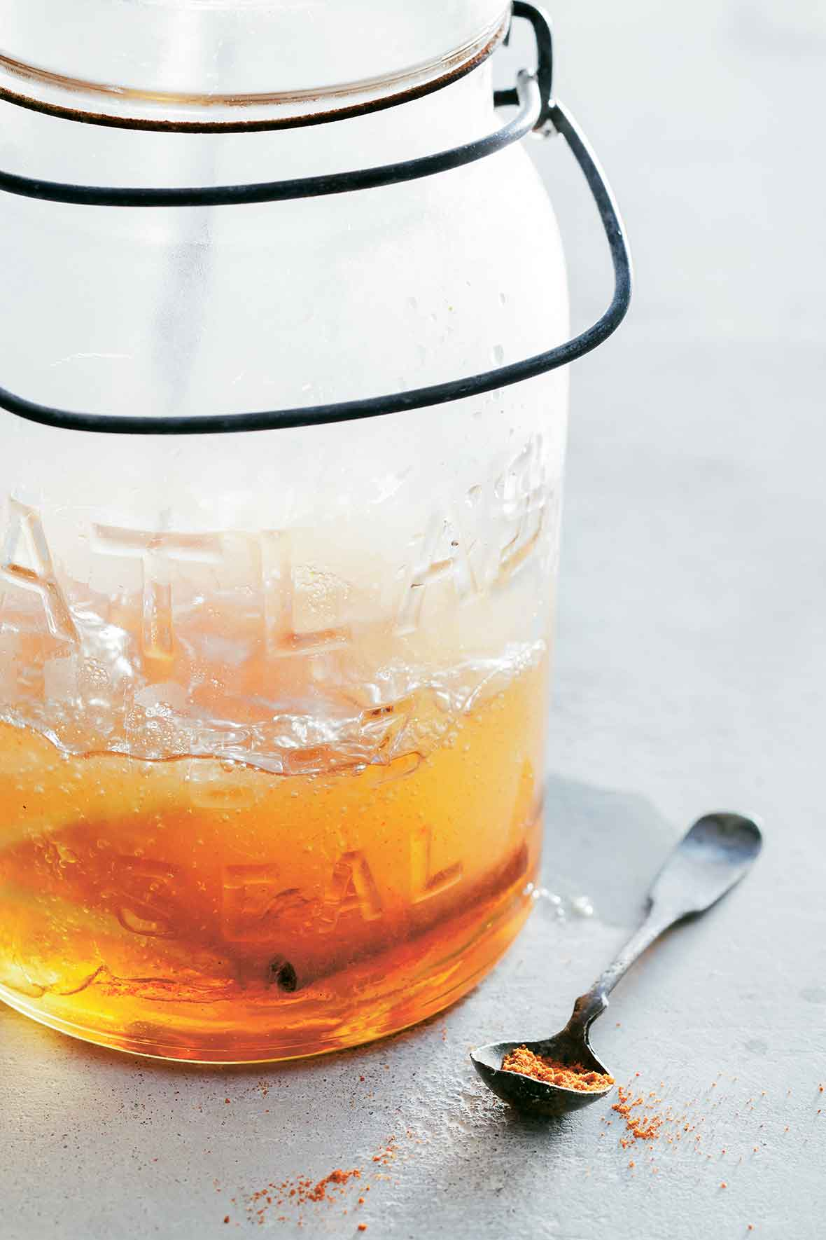 Glass jar with a cold and flu drink with a cinnamon stick, a spoon with ginger