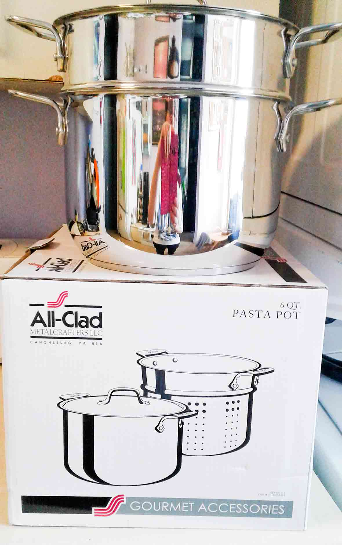 An All-Clad pasta pot sitting on its box