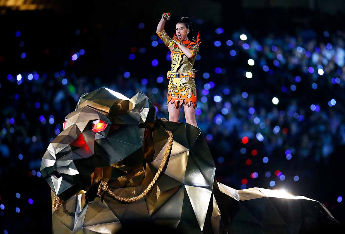Katy Perry singing on top of a huge golden tiger puppet