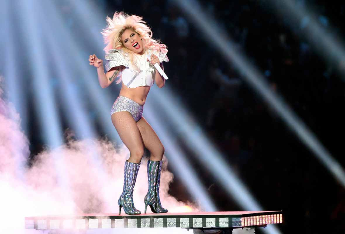 Lady Gaga is a bejeweled football outfit and high-heel boots singing