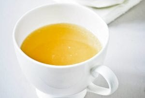 A white mug of chicken stock