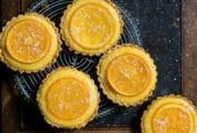 Five small tarts filled with orange curd and topped with candied orange slices on a cooling rack
