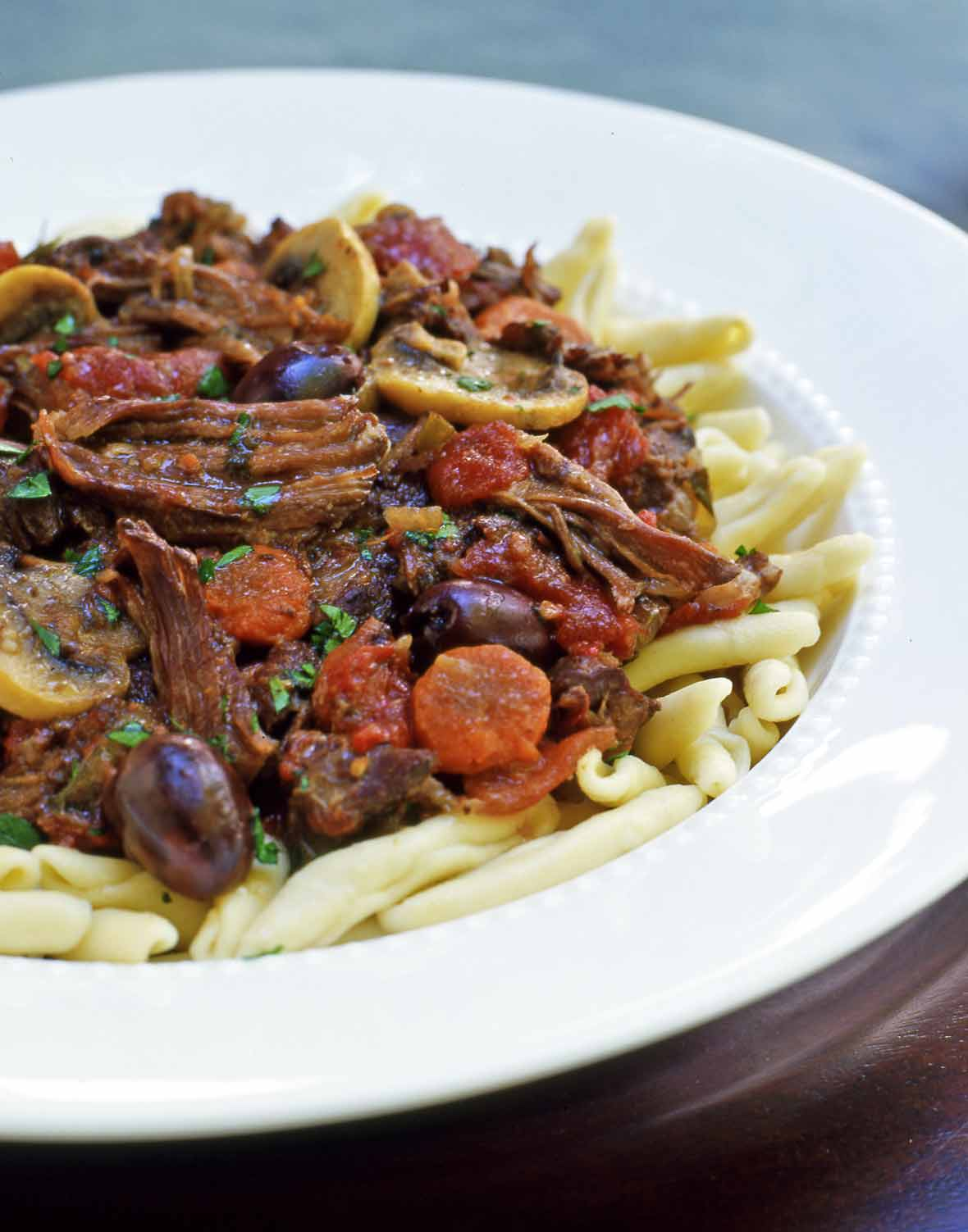 A white bowl filled with French beef stew piled atop pasta.