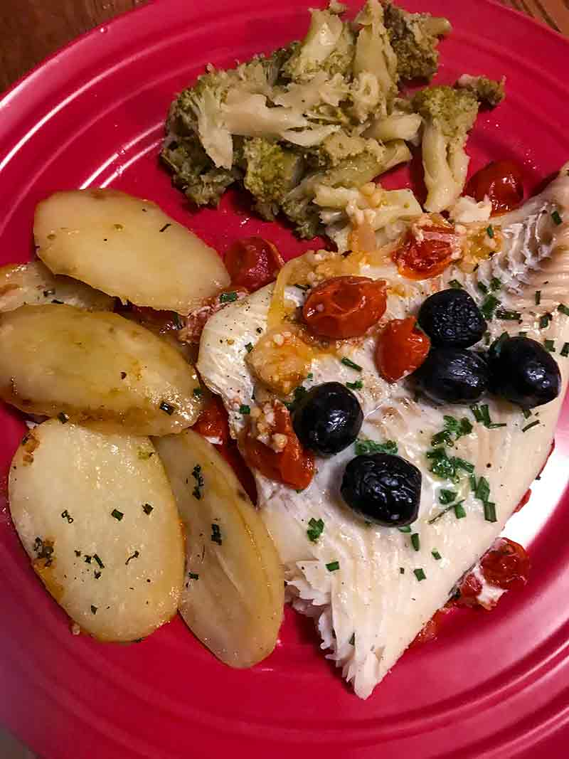 Red plate with baked fish with tomatoes and olives, roasted potatoes, broccoli