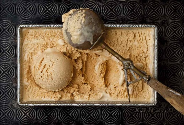 Salted caramel ice cream in a loaf pan on a pattern baking sheet with a scoop and scooper on top