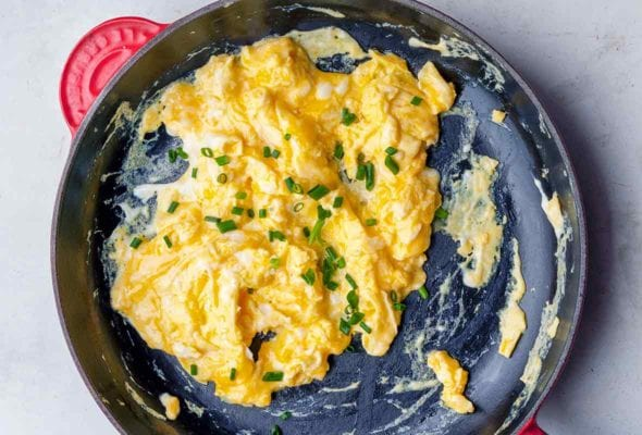 A nonstick skillet filled with scrambled eggs topped with chopped chives