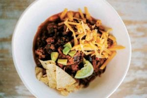 White bowl of beef chili with grated cheese, tortilla chips, and lime wedges on wood