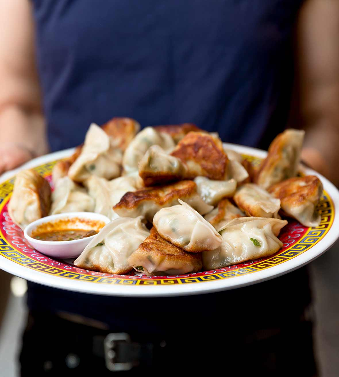 Person holding a plate of fried pork dumplings, with a bowl of black pepper scallion dipping sauce