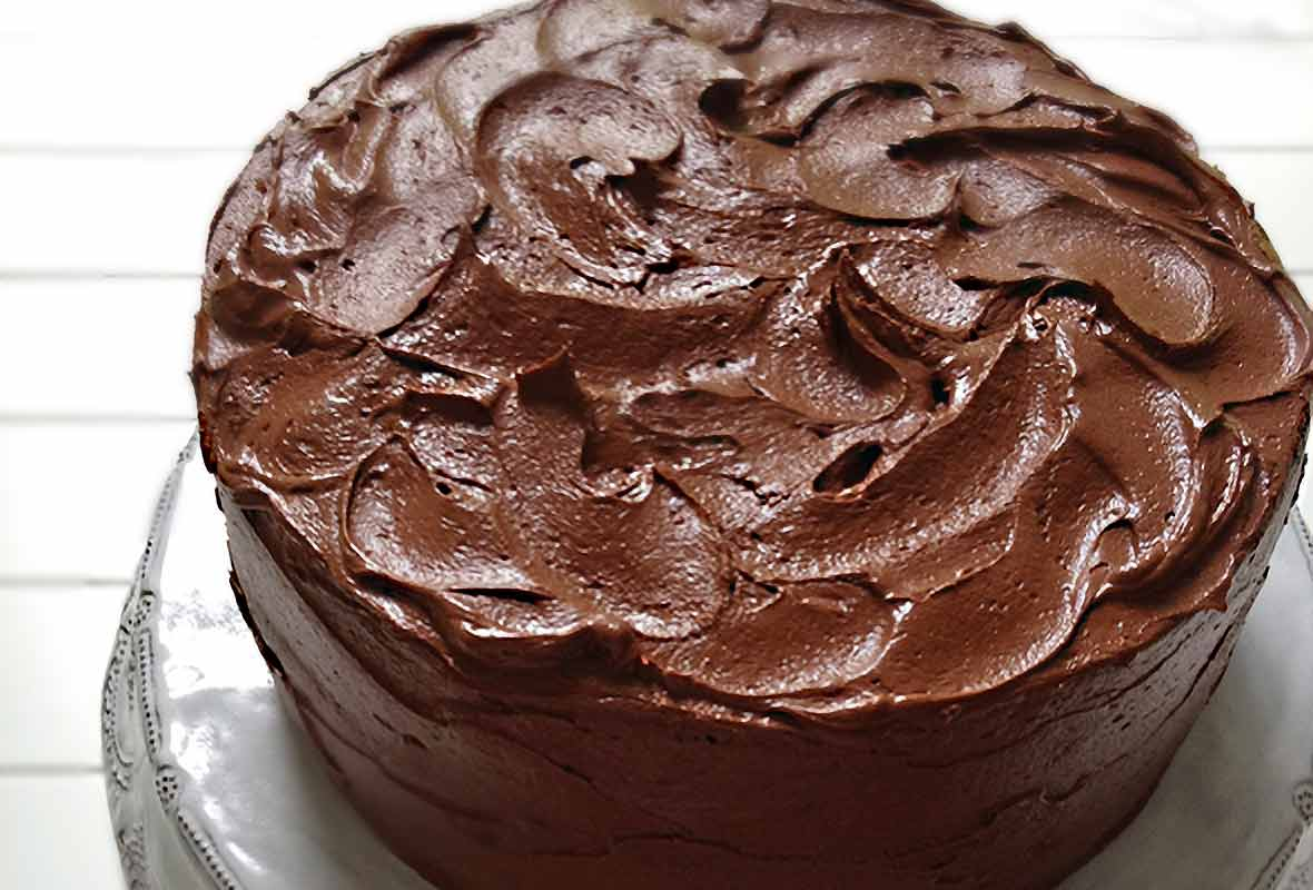 A Hershey chocolate cake with swirled chocolate frosting on a white cake stand