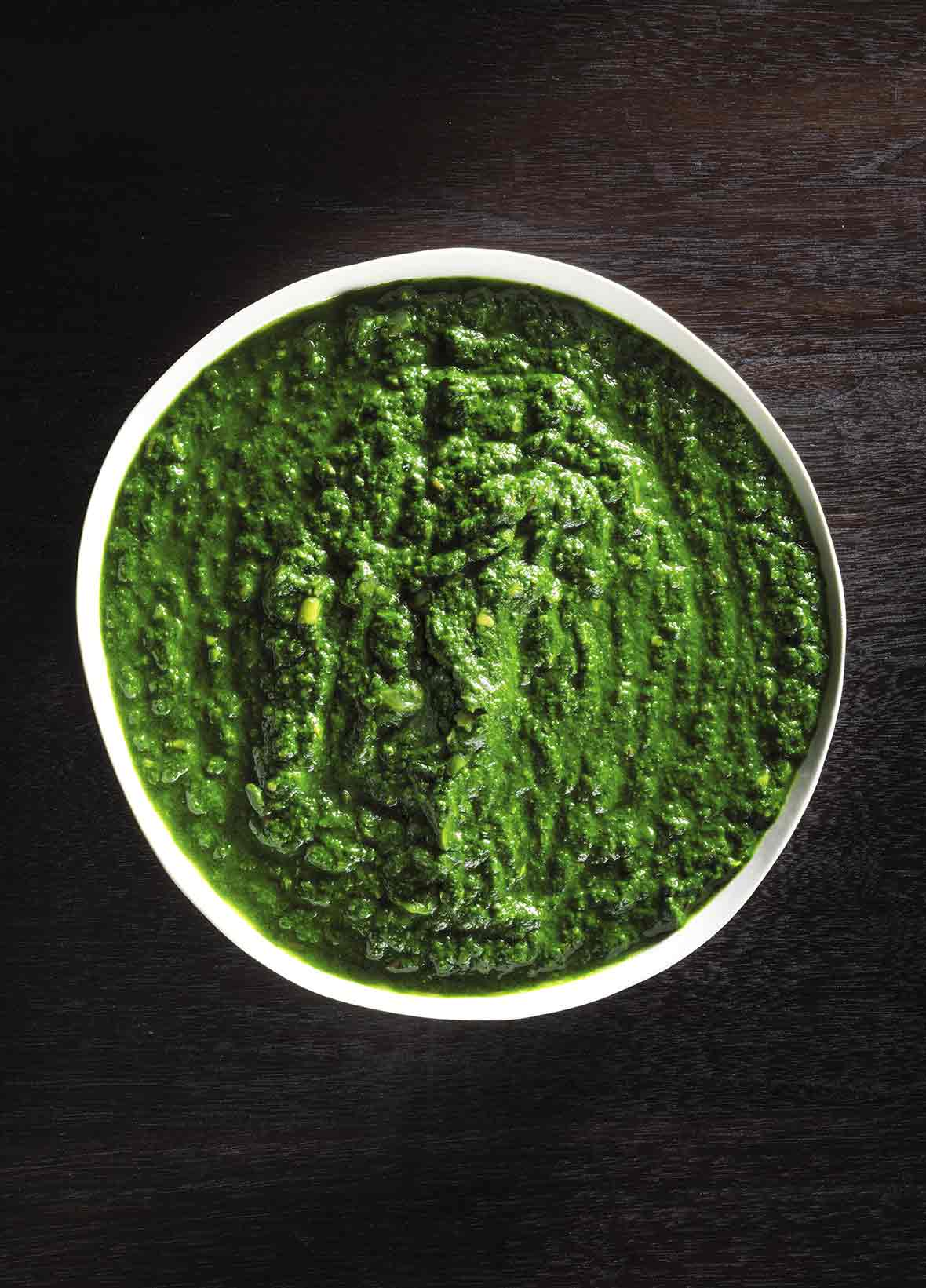 Bowl of Indian creamed spinach on black wood