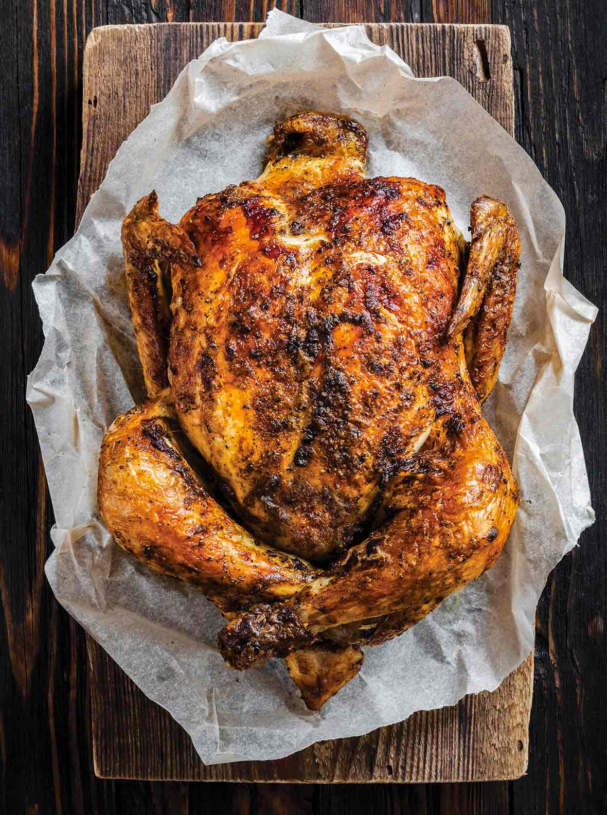 Spiced and herbed whole chicken, made in an Instant Pot, on parchment paper on a cutting board