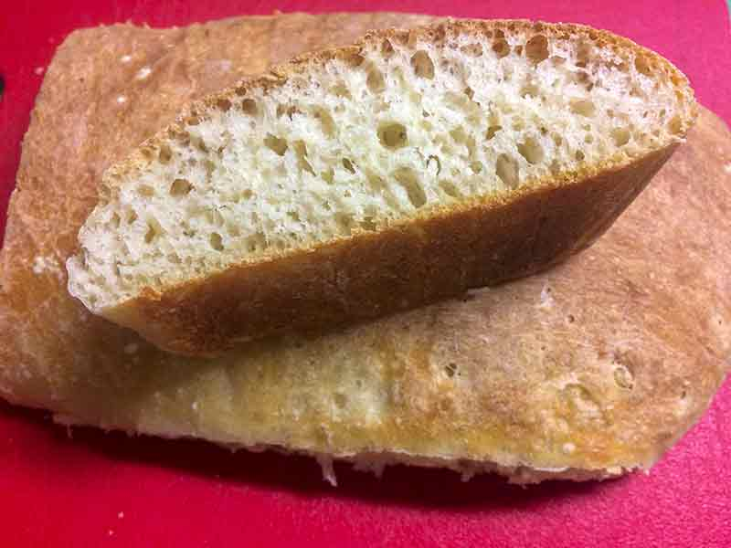 Loaf of Italian ciabatta bread sliced in half, with one half facing up to see the inside