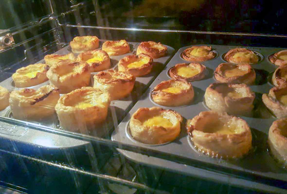 Two muffin tins in an oven filled with pasteis de nata or Portuguese custard cups