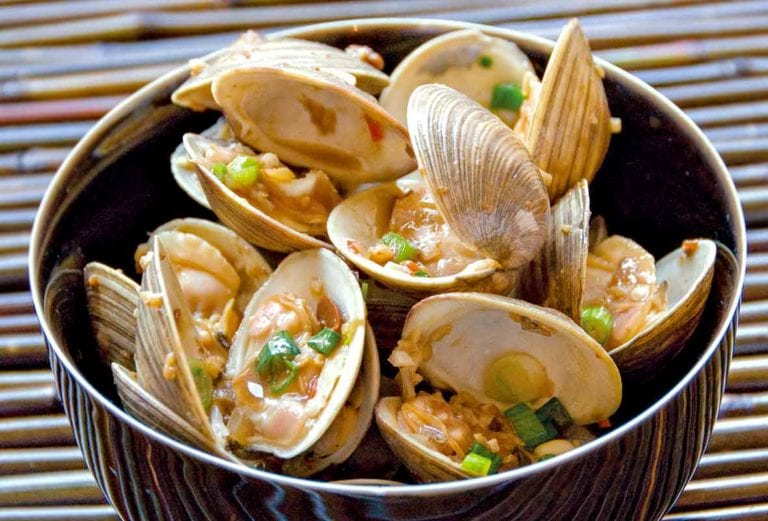 Bowl of stir-fried clams with chopped shallots, garlic, ginger, and chili flakes on bamboo
