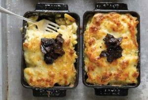 Two individual baking dishes with mac and cheese, topped with truffles