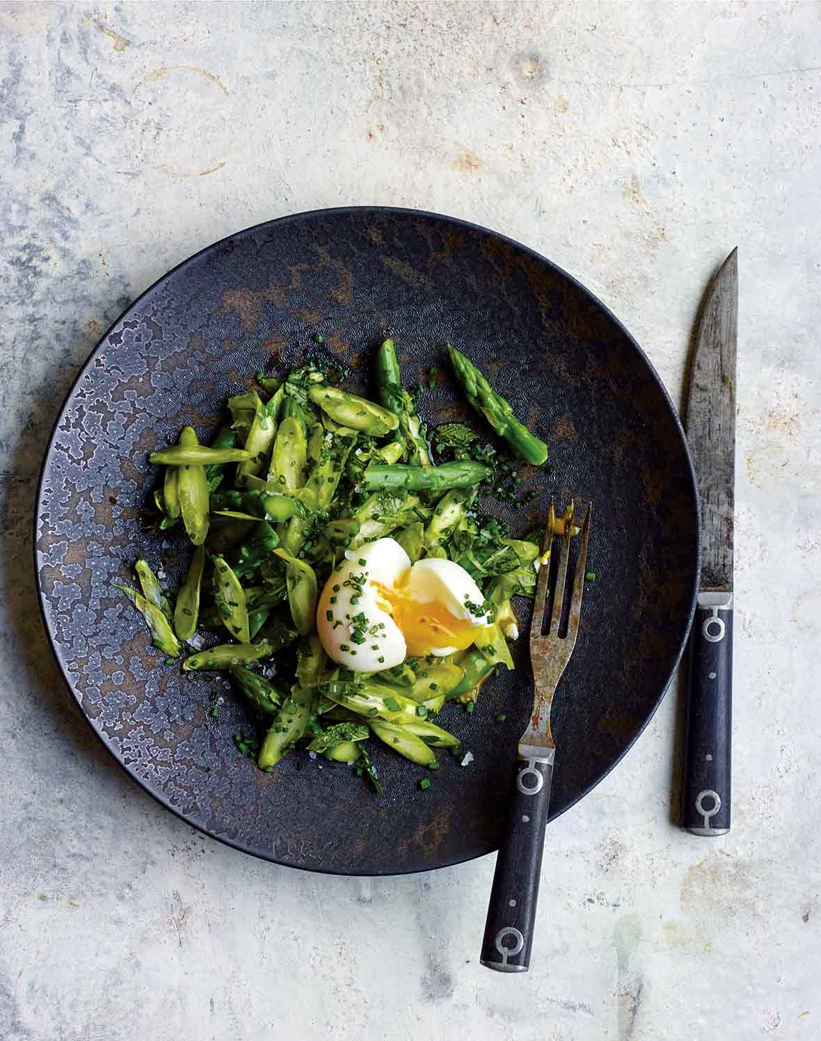 Asparagus and herb salad with chopped parsley, basil, tarragon, and mint and a broken soft boiled egg on a plate, fork and knife