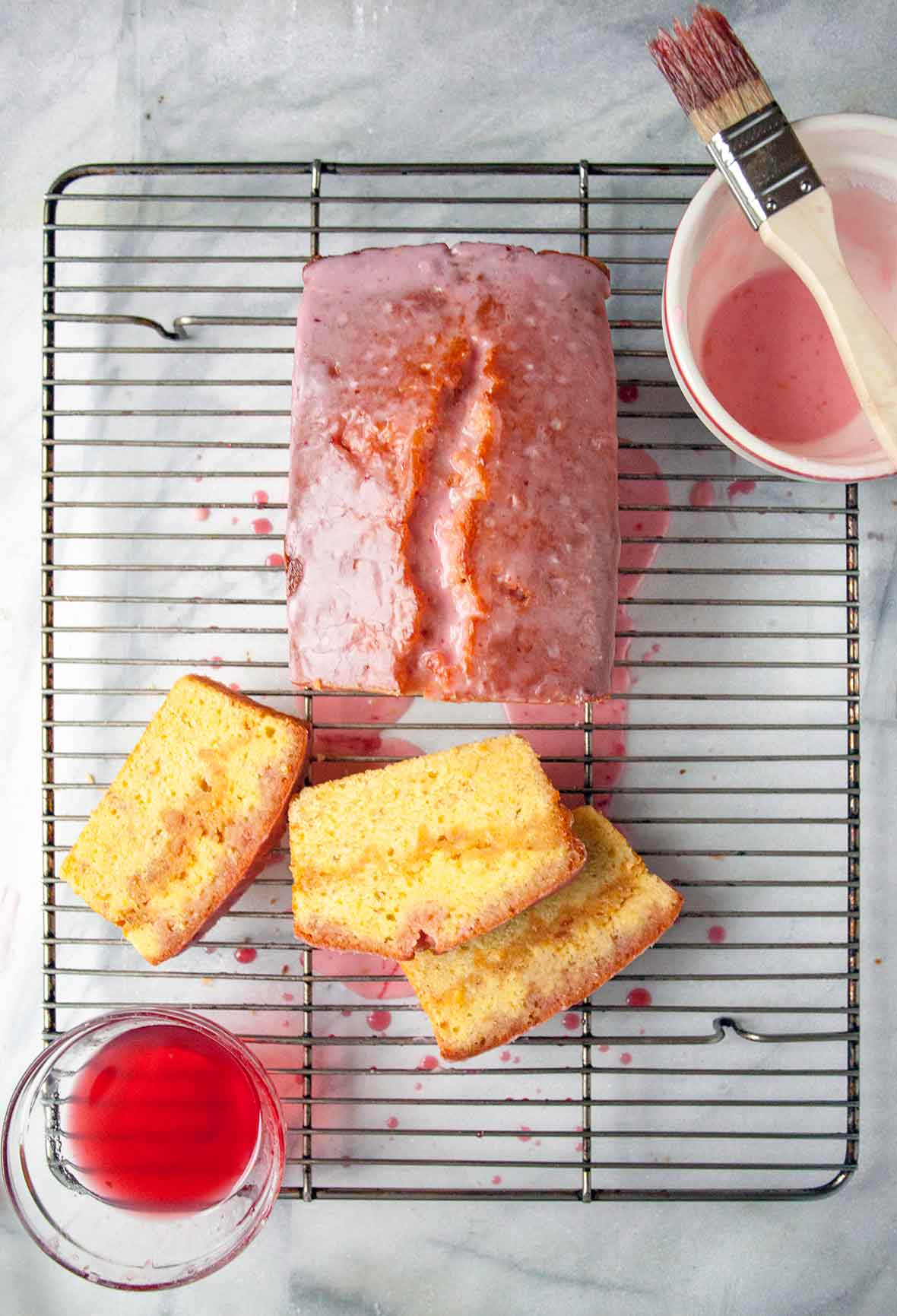 A blood orange pound cake on a wire rack with glaze and sugar syrup, three slices cut