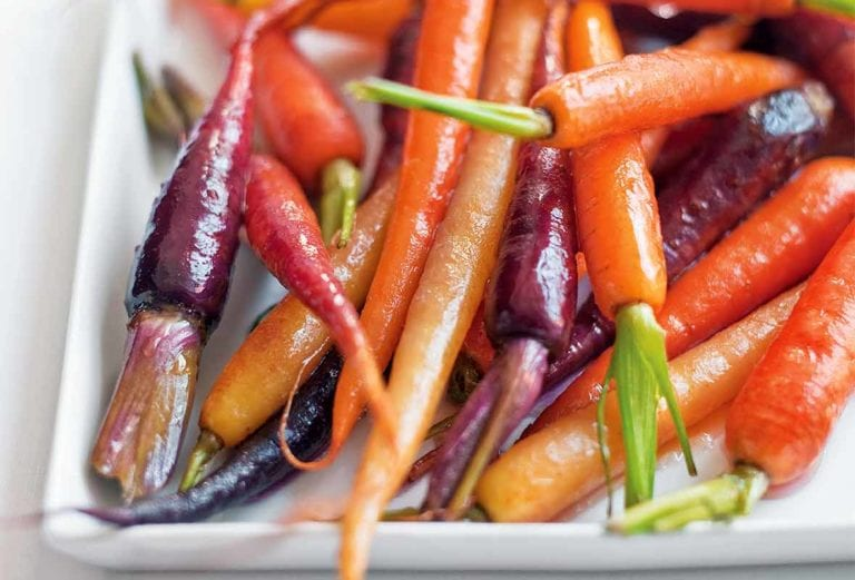 White plate filled with orange, purple, and yellow candied carrots