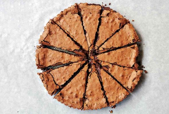 Chocolate tart cut into 12 slices on parchment paper