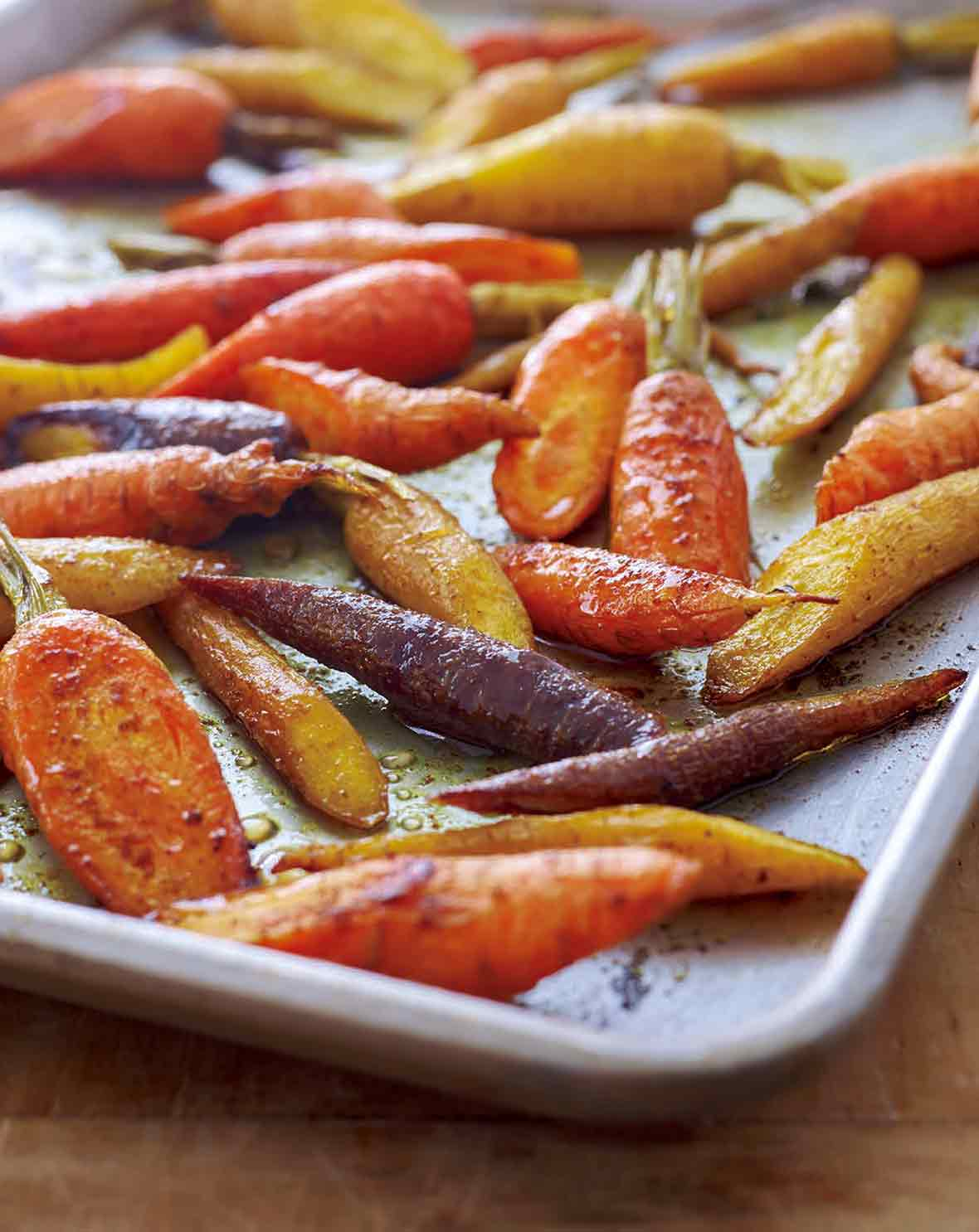 A baking sheet filled with orange, yellow, and purple curried roasted carrots