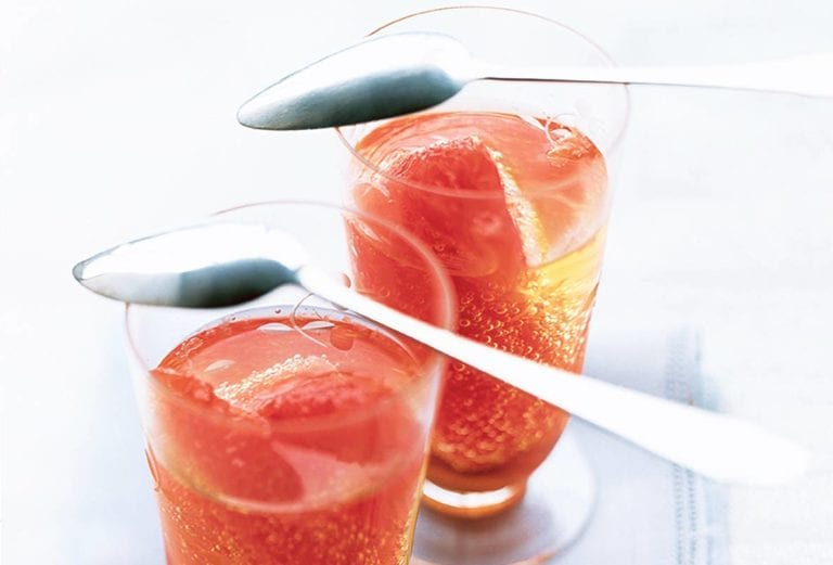 Two cordials glasses each filled with Moscato and a grapefruit section, on top are spoons