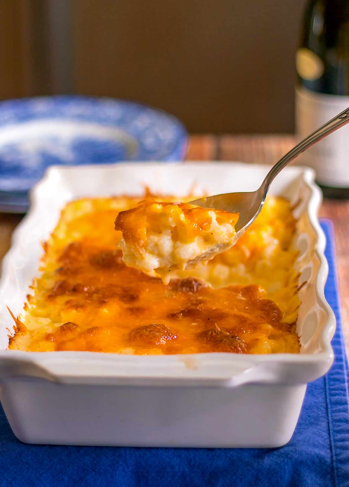 A casserole dish of hominy au gratin--hominy in a cheese sauce--plus a spoon filled with the cheesy hominy