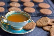 Cup of tea with a molasses spice cookie on the saucer, more cookies in a pile and on a wire rack