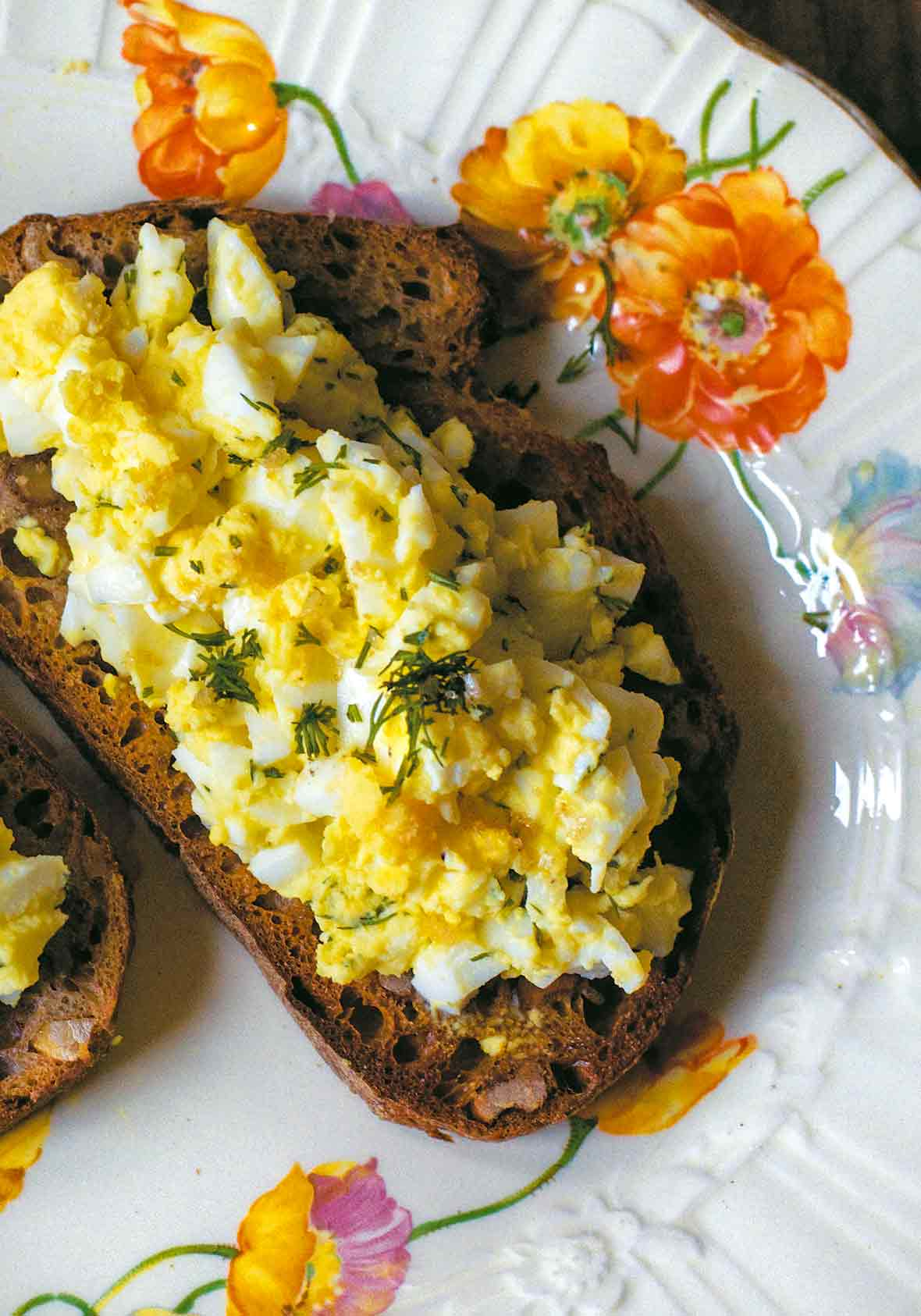 An open face egg salad sandwich on toasted whole wheat