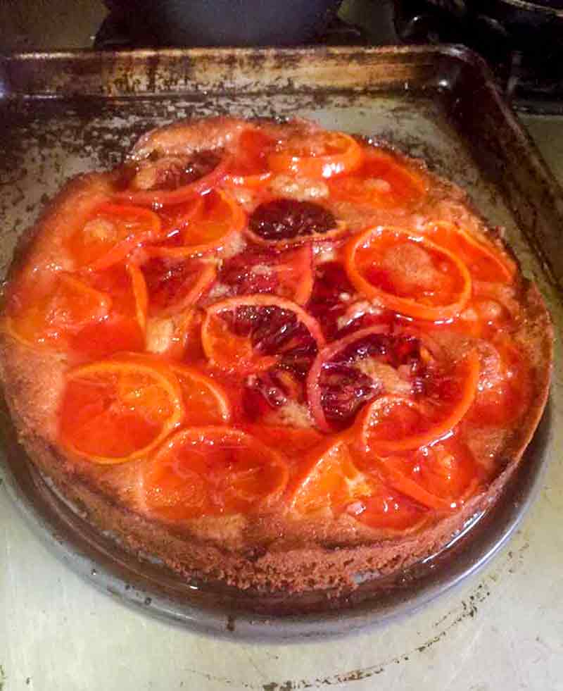 A clementine cake topped sliced oranges, blood oranges, and clementines on a baking pan