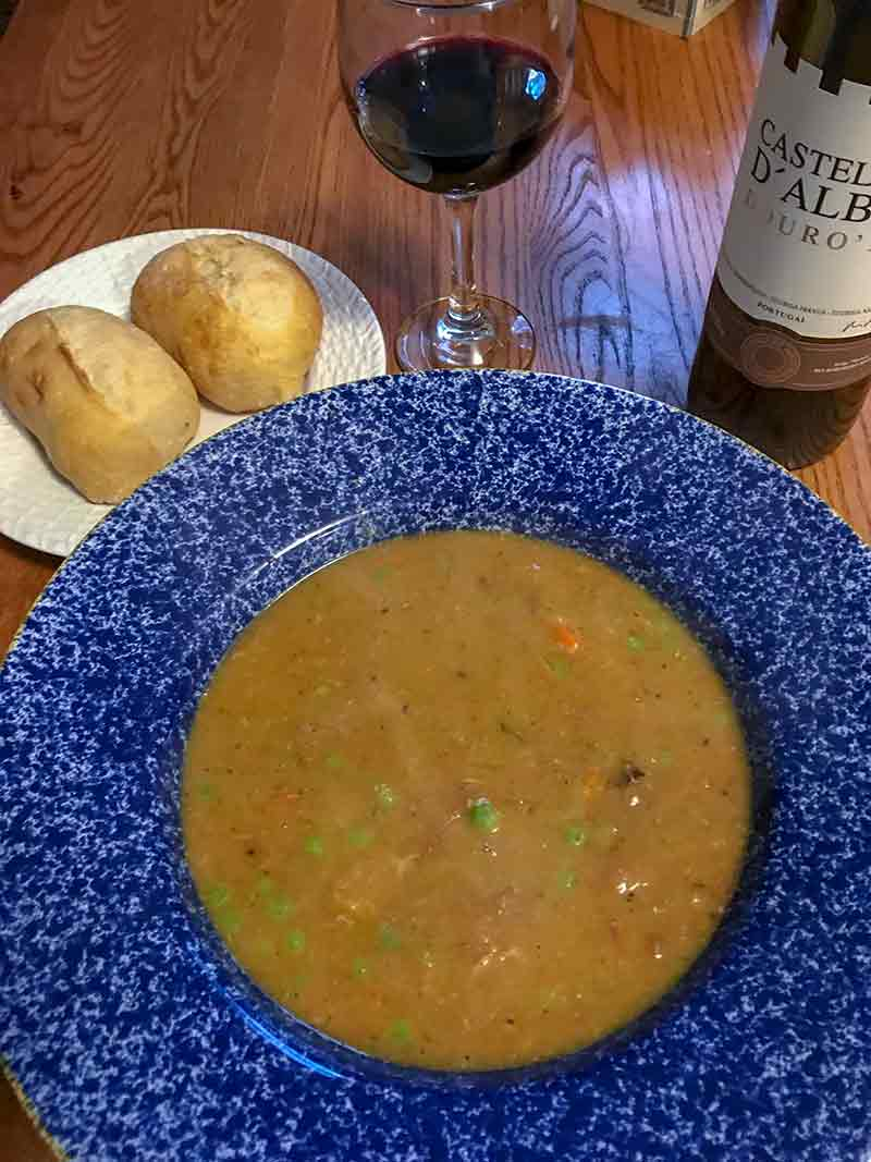 Blue bowl of slow-cooker pea soup, plate of two rolls, bottle of wine on a table