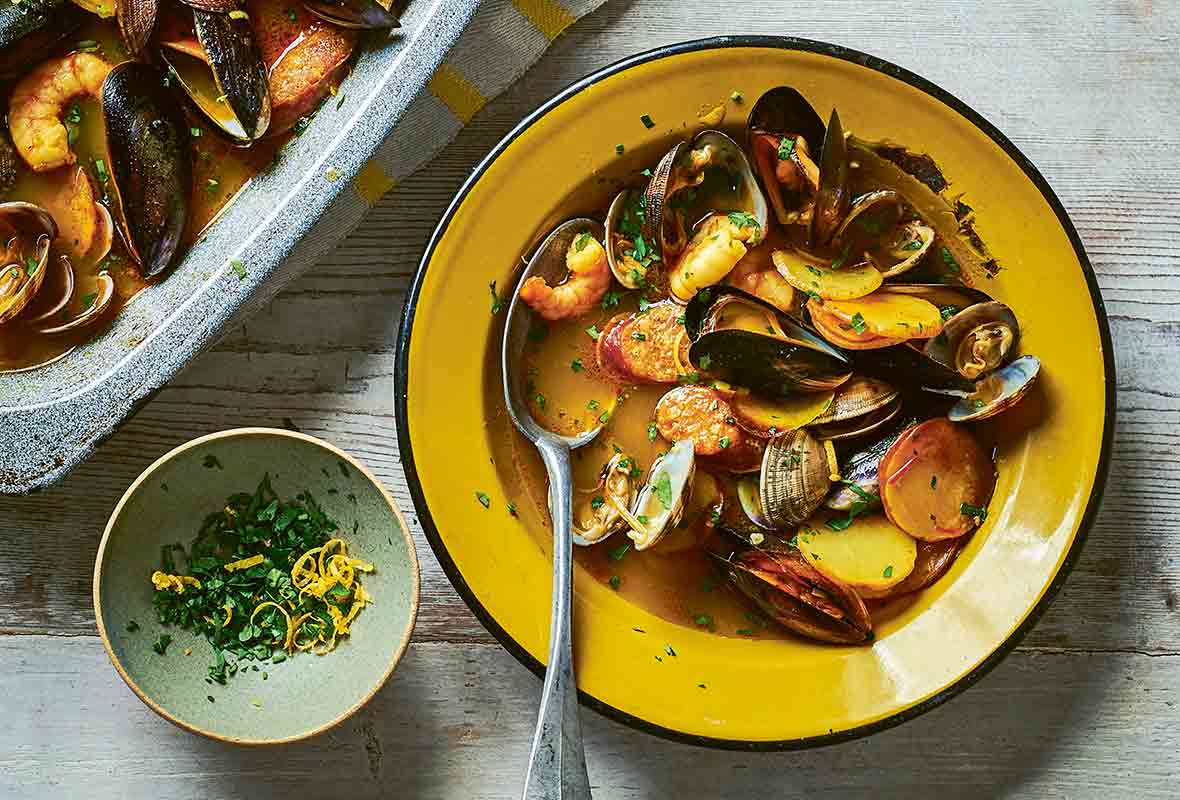Sheet pan and a yellow bowl filled with seafood stew of mussels, shrimp, clams, chorizo, and potatoes