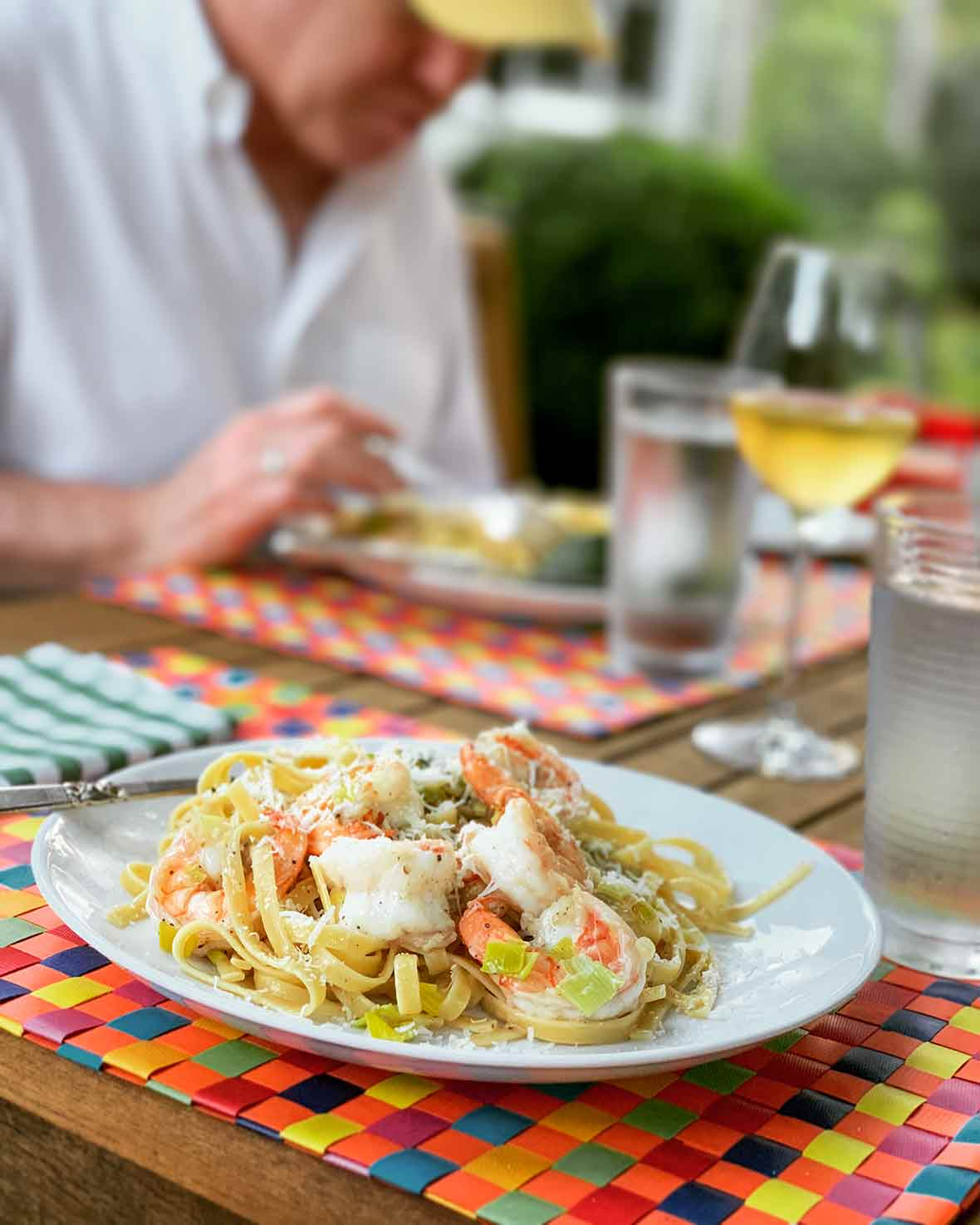 A white plate filled with shrimp and leek pasta on a multi-colored woven placemat.