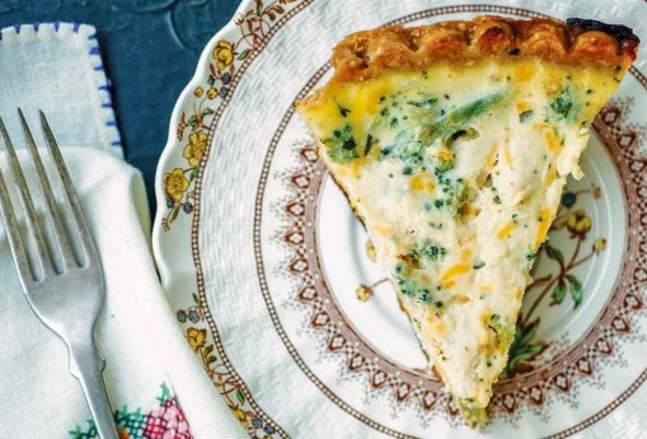 A plate with a slice of broccoli Cheddar quiche