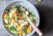 Bol of finely chopped celery root salad with chunks of clementines, pumpkin seeds, and parsley