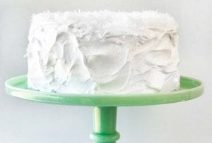 A white coconut layer cake, with 7-minute frosting topped with shredded coconut on a green cake stand