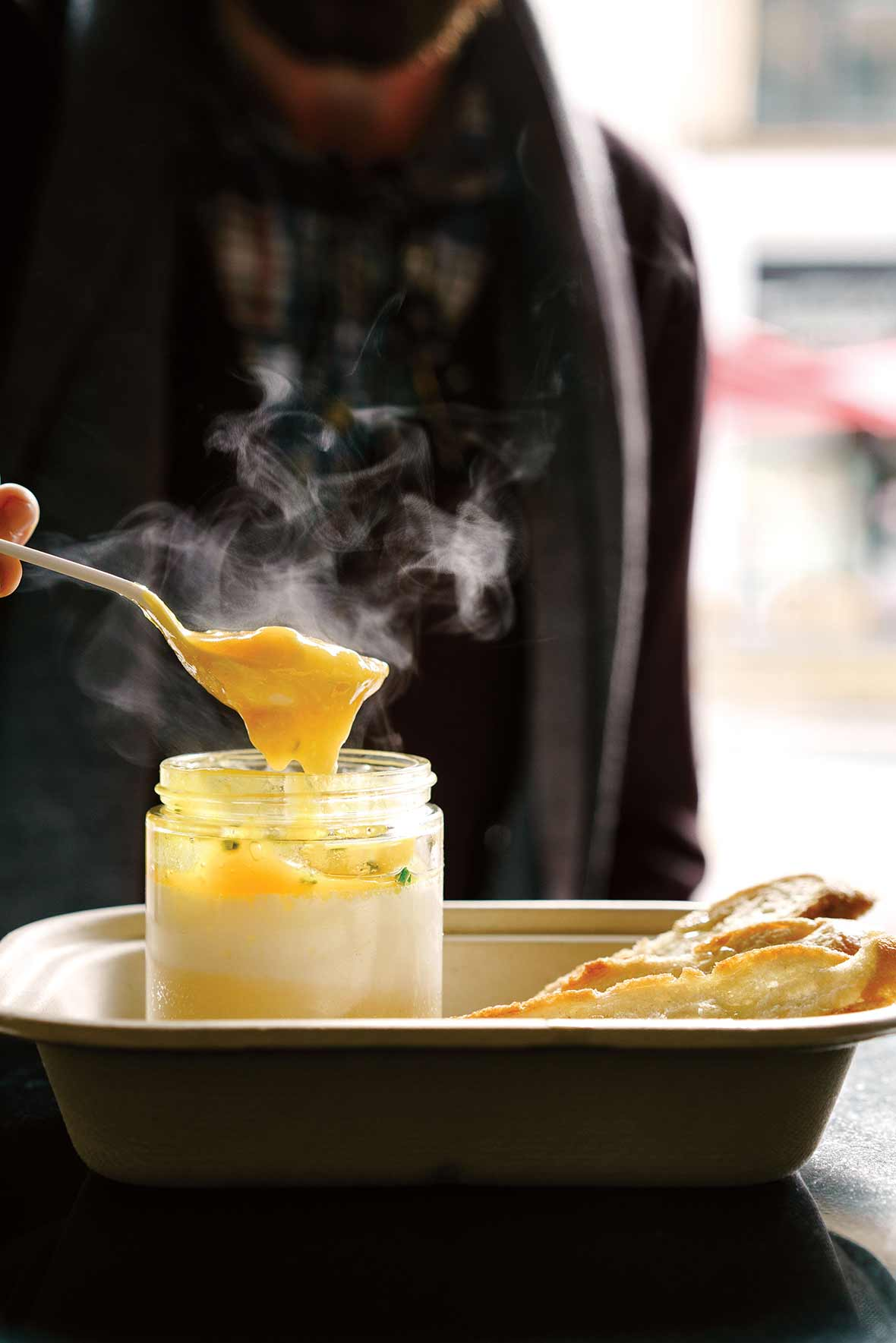 Person with a spoon digging into a glass jar of coddle eggs with potato puree underneath, slice of bread nearby